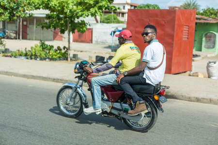 means of transportation: Cotonou, Benin: May 26: A man rides a hired Motorcycle taxi, the most common means of hired transportation in the city, on May 26, 2015 in Cotonou, Benin.
