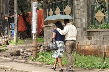 drizzling rain: Addis Ababa - July 26: A couple walk holding their umbrella in the drizzling rain on a typical winter day during the rainy season on June 26, 2015 in Addis Ababa, Ethiopia.