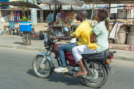 means of transportation: Cotonou, Benin: May 26: A woman rides a hired Motorcycle taxi, the most common means of hired transportation in the city, on May 26, 2015 in Cotonou, Benin. Editorial
