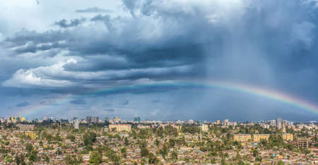 addis: Aerial view of the city of Addis Ababa covered by a rainbow and dark clouds Stock Photo