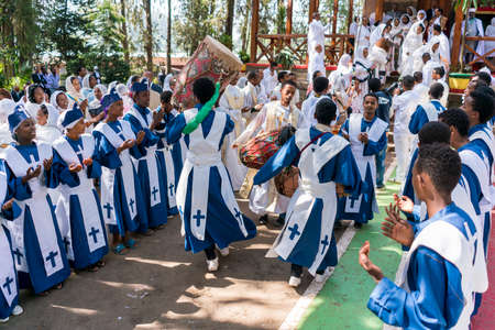 accompanied: ADDIS ABABA, ETHIOPIA - May 21: A young member of the Ethiopian Orthodox Church Choir sing and chant accompanied by a drum during a colorful procession on May 21, 2016 in Addis Ababa, Ethiopia