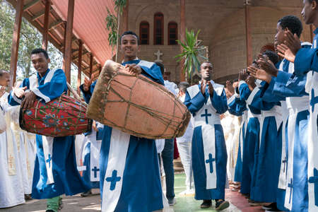 addis: ADDIS ABABA, ETHIOPIA - May 21: A young member of the Ethiopian Orthodox Church Choir sing and chant accompanied by a drum during a colorful procession on May 21, 2016 in Addis Ababa, Ethiopia