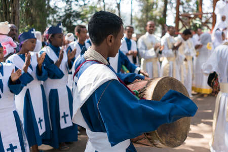 religious clothing: ADDIS ABABA, ETHIOPIA - May 21: A young member of the Ethiopian Orthodox Church Choir sing and chant accompanied by a drum during a colorful procession on May 21, 2016 in Addis Ababa, Ethiopia