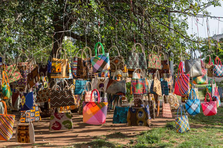 A street market in Maputo, Mozambique where hand crafted bags are displayed by hanging them on a tree Banco de Imagens