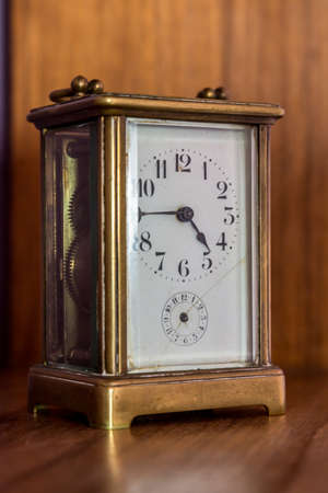 minute hand: An old desk top clock with analog hour and minute hand on a shelf