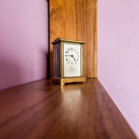 An old desk top clock with analog hour and minute hand on a shelf