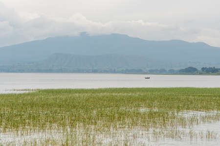 The beautiful Hawassa lake surrounded by lush vegetation and mountains at a distance
