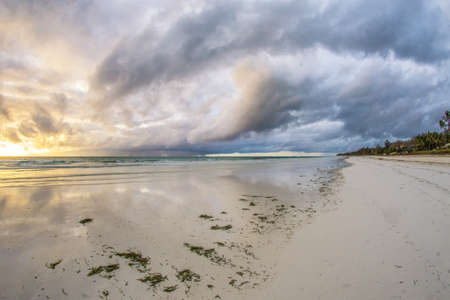 Beautiful sunrise behind the thunderous clouds over the white sand beaches of Diana Beach in Mombasa Kenya