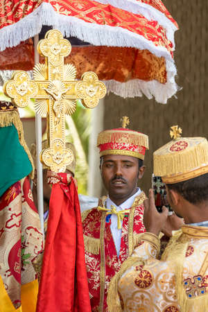 Addis Ababa - Jan 19: A priest wearing a colorful traditional gown holding a large cross has his picture taken by another priels, during a Timket celebrations of Epiphany, on January 19, 2017 in Addis Ababa, Ethiopia.