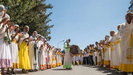 Addis Ababa - Jan 19: Young girls dressed in colorful traditional clothing sing and chant while accompanying the Tabot, a model of the arc of covenant, during a Timket procession as part of celebrations of Epiphany, on January 19, 2017 in Addis Ababa, Eth Redakční