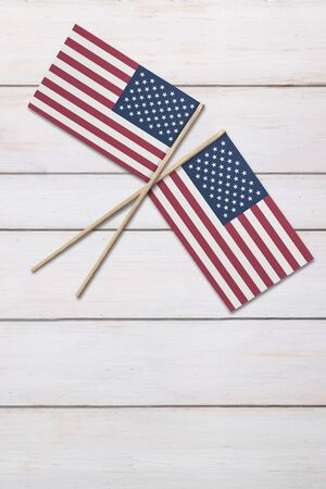 Two United States flags on a painted wood background