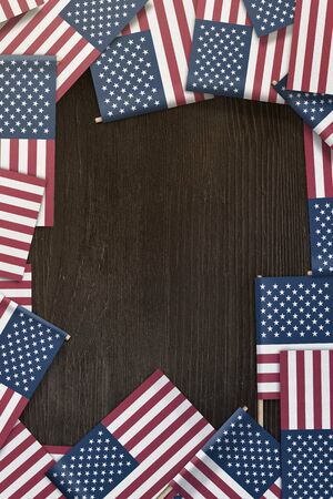 United States small flags framing a wood texture background with copy space