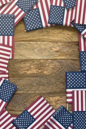 small United States flags framing a wood texture background with copy space