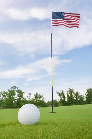 United States of America flag on golf course putting green with a ball near the hole Foto de archivo