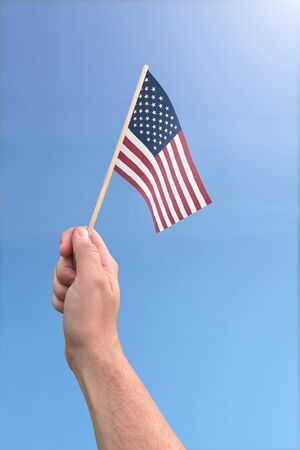 United States flag held by a hand in front of a sunny blue sky Foto de archivo