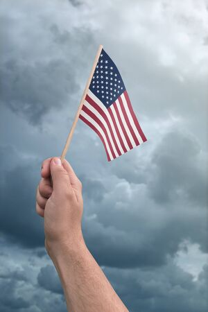 United States flag held by a hand in front of a cloudy stormy sky Foto de archivo