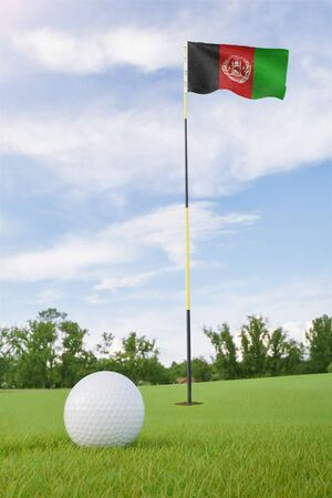 Afghanistan flag on golf course putting green with a ball near the hole Foto de archivo