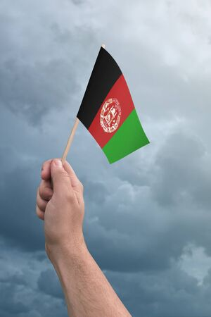Afghanistan flag held high in the air with a cloudy sky