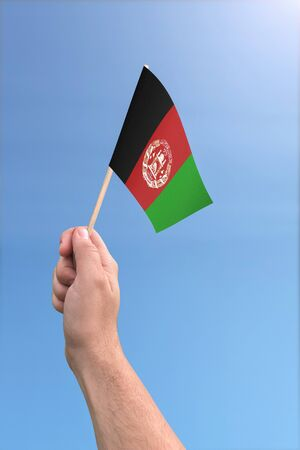 Afghanistan flag held high in the air with a clear sky