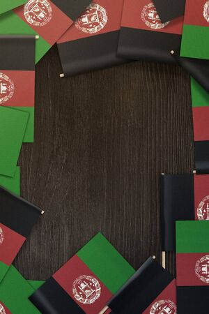 small Afghanistan flags framing a wood texture background with copy space