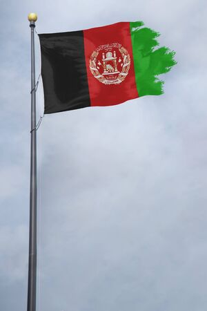 Afghanistan Flag with a torn edge in front of a stormy sky Foto de archivo