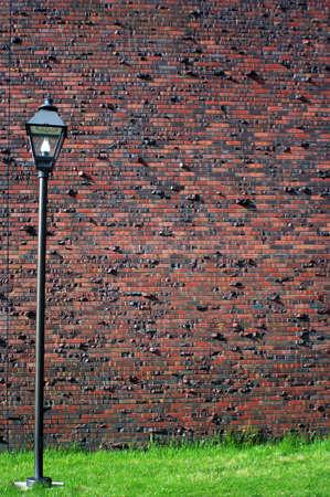 a red brick wall with a lamp and green grass