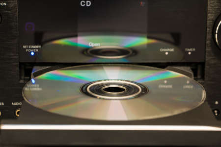 optical disk: Selective focus cd and its reflection on the surface of a cd player Stock Photo