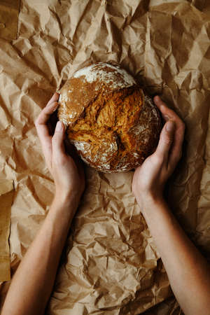 craft background: hands holdig bread on the craft background