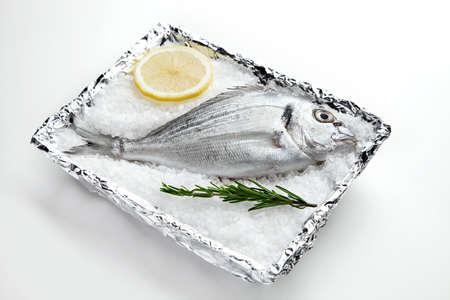 dorada: Raw dorada on sea salt in plate covered with foil