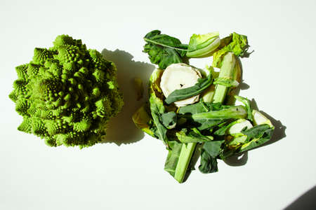 haulm: Haulm and romanesco cabbage broccoli in direct sunlight on white table top view