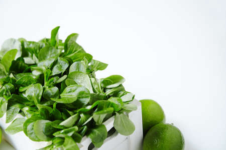 berros: Watercress salad in white wooden box with limes around close up