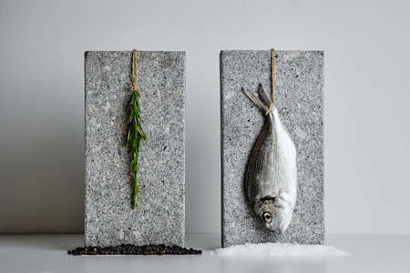 dorada: Dorada and rosemary presented on stone bricks with sea salt and black pepper