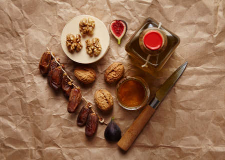 formagi: Datils, walnuts, figs and olive oil on craft brown paper top view