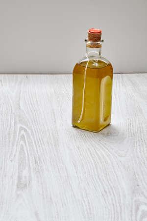 formagi: Bottle of artisian olive oil virgin extra isolated on wooden table