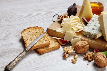 formagi: Close up Four cheeses with supplements, dried bread, figs and other  top view on white table Stock Photo