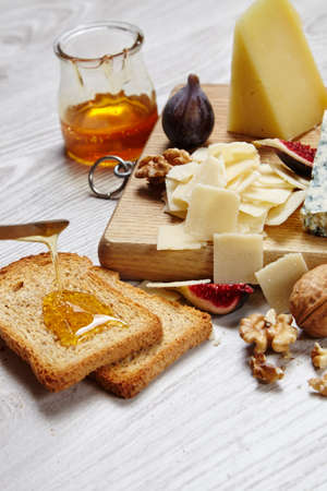 formagi: Close up four cheeses with supplements, dried bread topped with honey on white wooden table