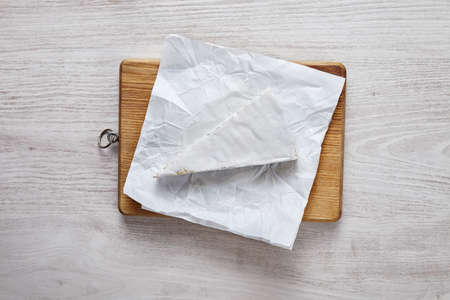 formagi: Brie uncovered on wooden brown plate on white table isolated top view