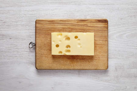 formagi: Emmental cheese isolated on wooden board on white brushed farm table