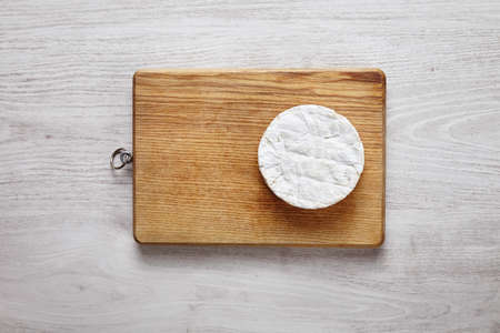 formagi: Camembert on side of the chopping wooden board on brushed white table top view Stock Photo