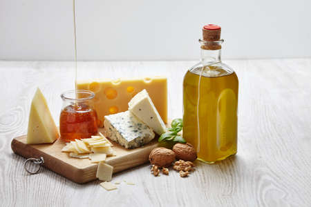 formagi: four cheeses with supplements on chopping board an white wooden table side view