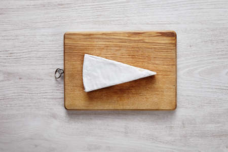 formagi: whole soft Brie isolated on choppping board on white wooden table top view