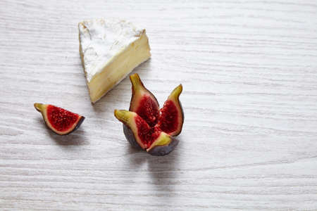 formagi: Camembert piece with splitted figs on whte wooden table Stock Photo