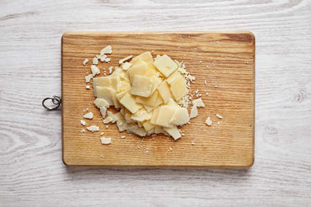formagi: Parmesan sliced, isolated on wooden desk on white table top view Stock Photo
