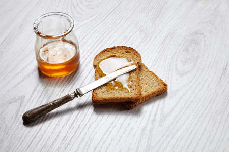 formagi: Dried pan topped with honey on white table with antique knife Stock Photo