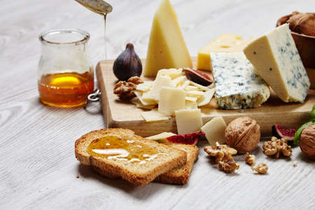 formagi: Four cheeses with supplements close up. dried bread topped with honey, figs, basil, walnut on white table