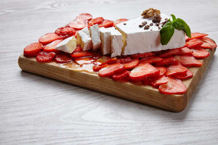 formagi: Brie cheese on strawberry covered wooden plate topped with honey and mint side view