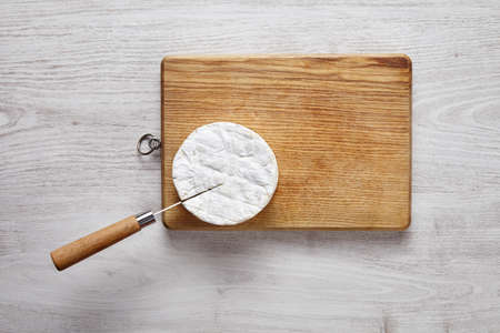 formagi: Cutting camembert top view knife brushed white table wooden board Stock Photo