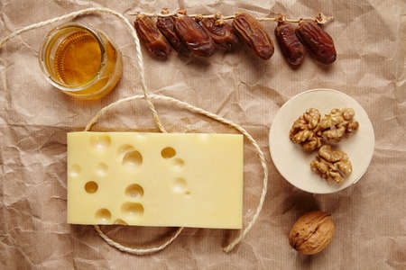 formagi: Emmental cheese with dried datils, walnut, honey on craft brown paper and rope