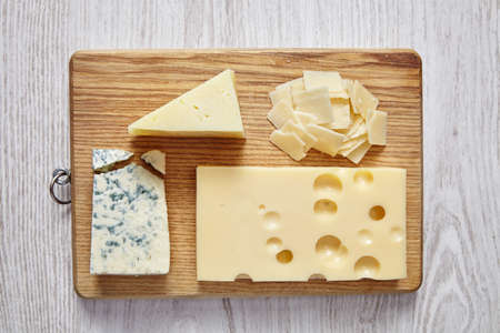 formagi: four cheeses on white wooden table and chopping board
