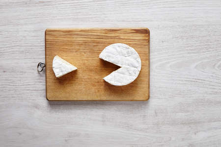 pacman: Camembert pacman style isolated on chopping board top view white brushed table